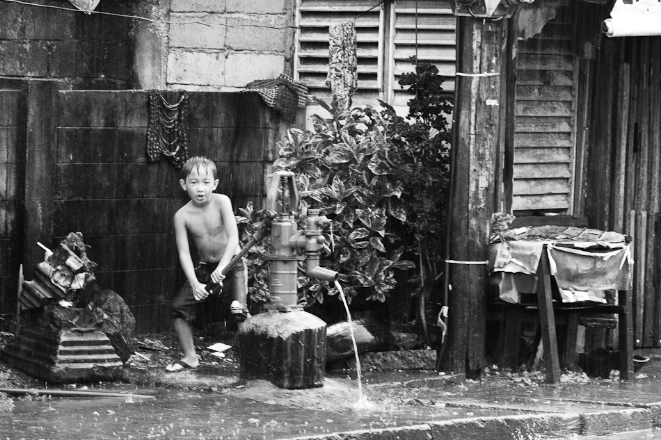 boy working a water pump
