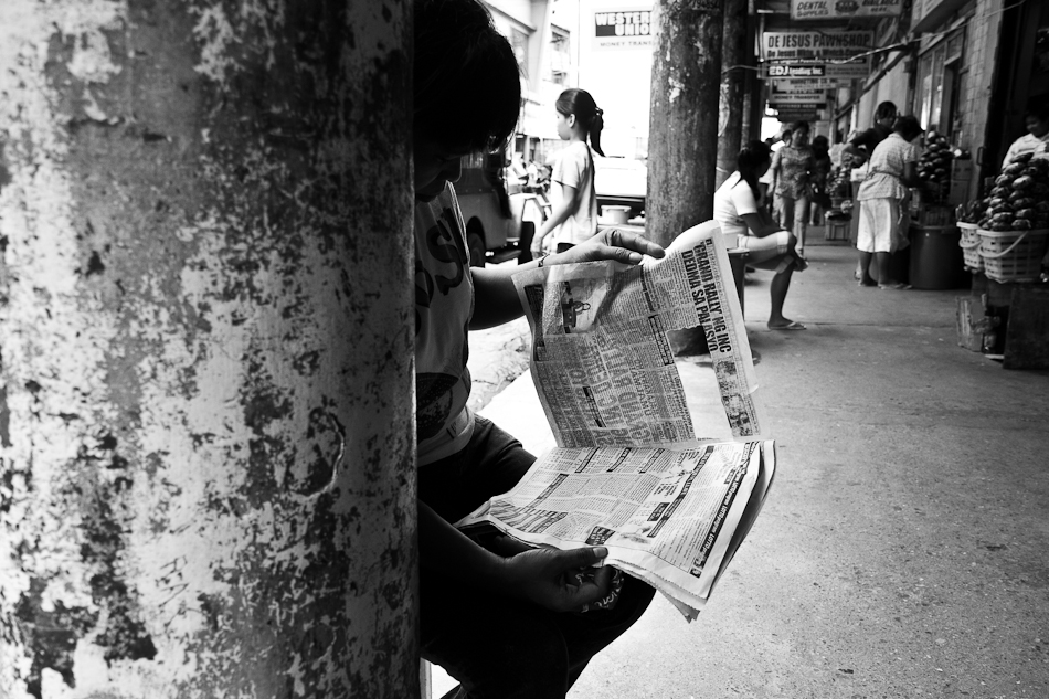 lady reading newspaper on the sidewalk