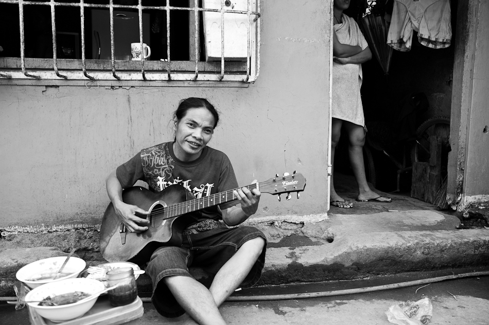 a man playing the guitar by the sidewalk