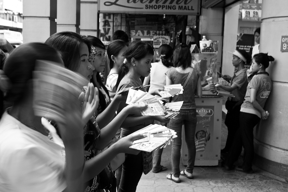 ladies line up outside a mall entrance selling prepaid GSM phone cards