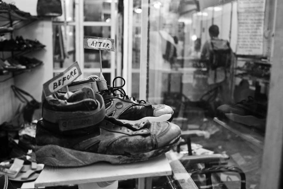 rubber shoes on display inside a showcase at the shoe repair shop. before and after