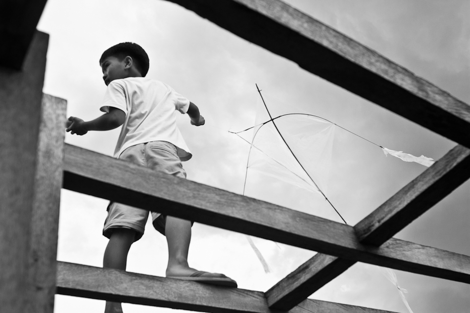 a boy balances on the boat frames while holding on to his kite