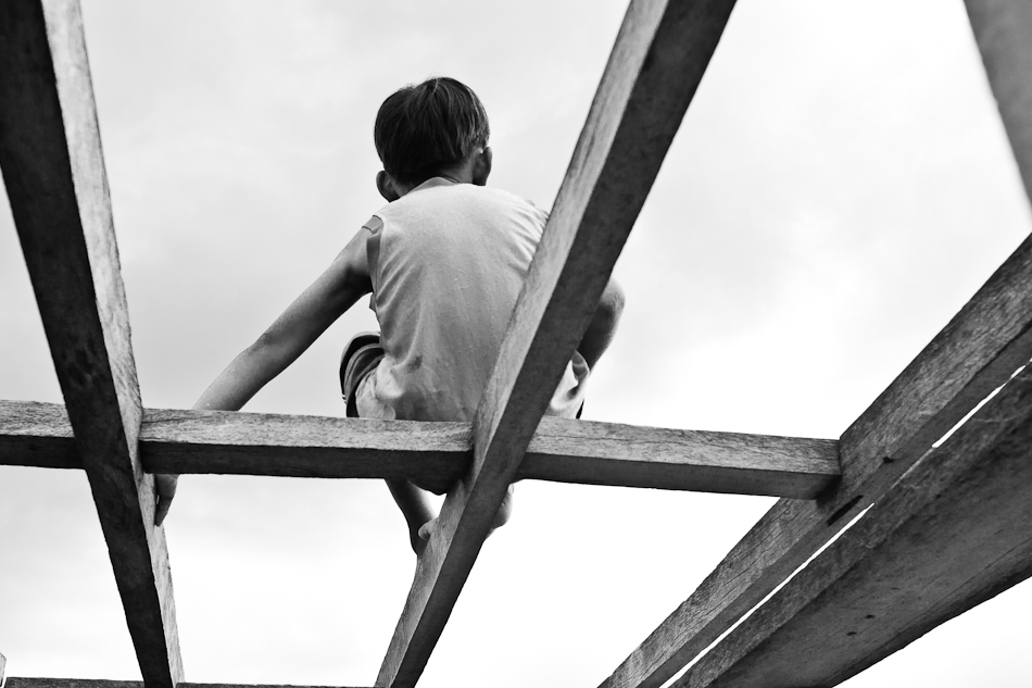 another boy sitting on the wooden boat frame