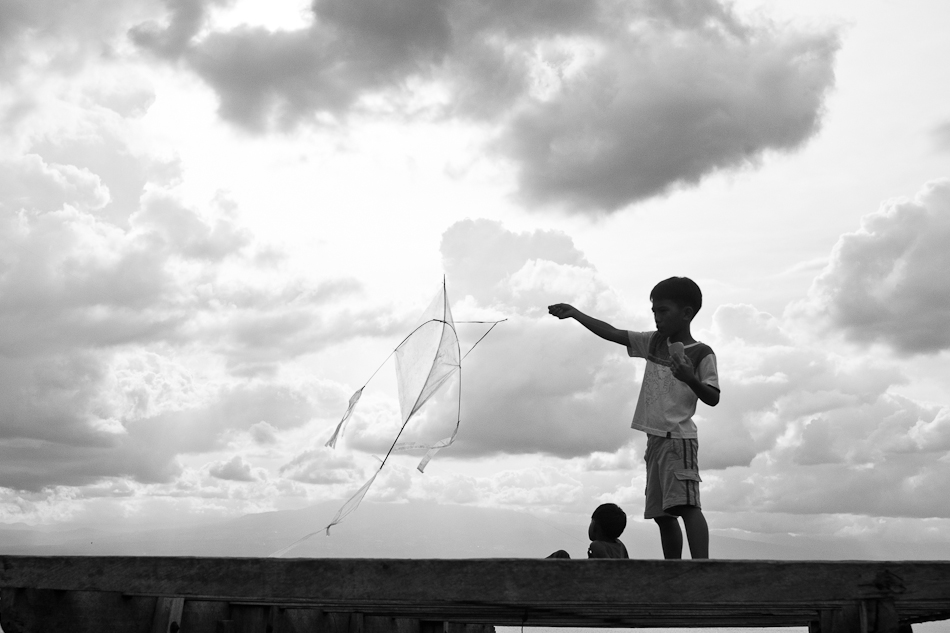 silhouette of two boys, their kite and the clouds