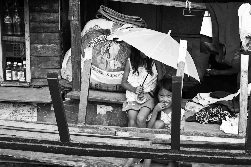 2 girls playing with an umbrella outside their house