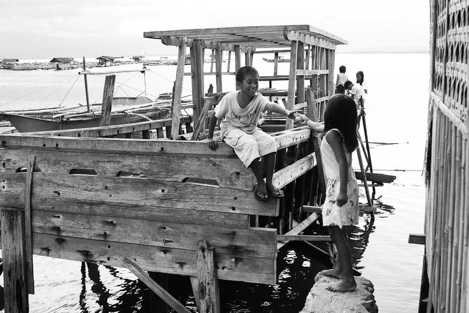 a girl hands out a piece of bread to a boy playing on the wooden boat frame.