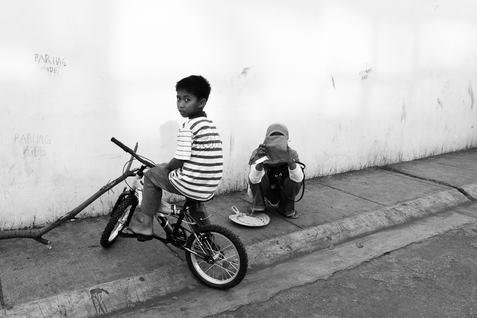 a boy on his bike on a sidewalk