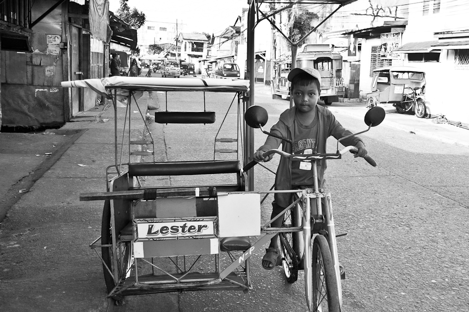 a little boy trying out an adult sized tricycle (pedicab)