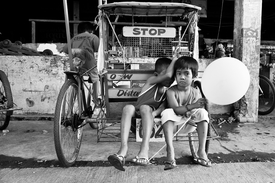 2 boys sitting at the back of a parked pedicab