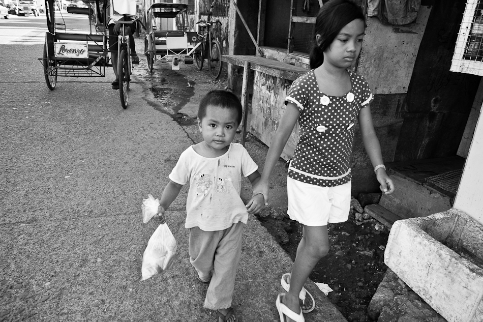 a girl holding his little brother who is holding a bag of bread for breakfast