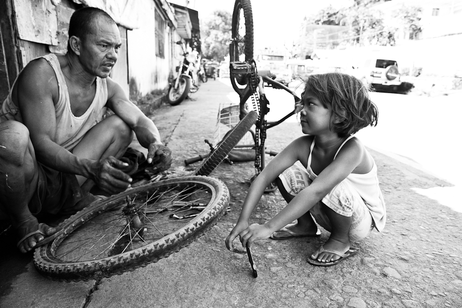 a man having a conversation with his daughter while fixing his bicycle