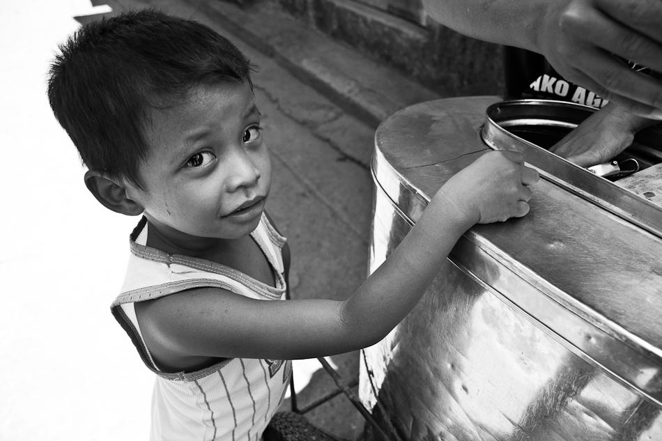 a sweaty little boy buying a cone of ice cream