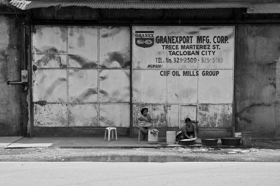two women minding their laundry in front of a closed warehouse
