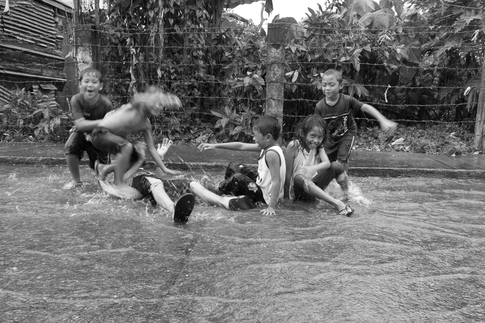 children playing on flooded water from a strong summer rain