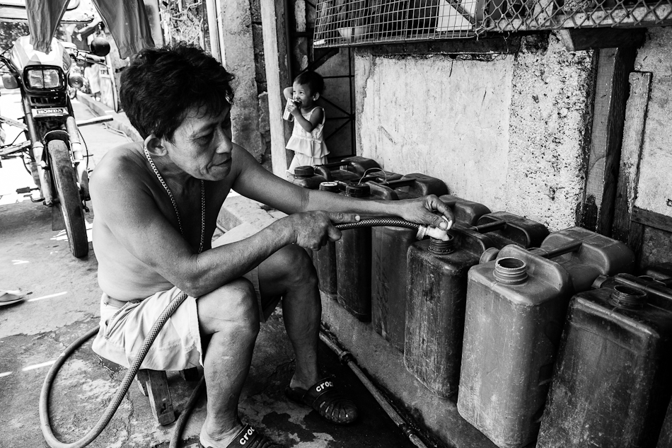 a man makes a living by selling water at a local neighborhood