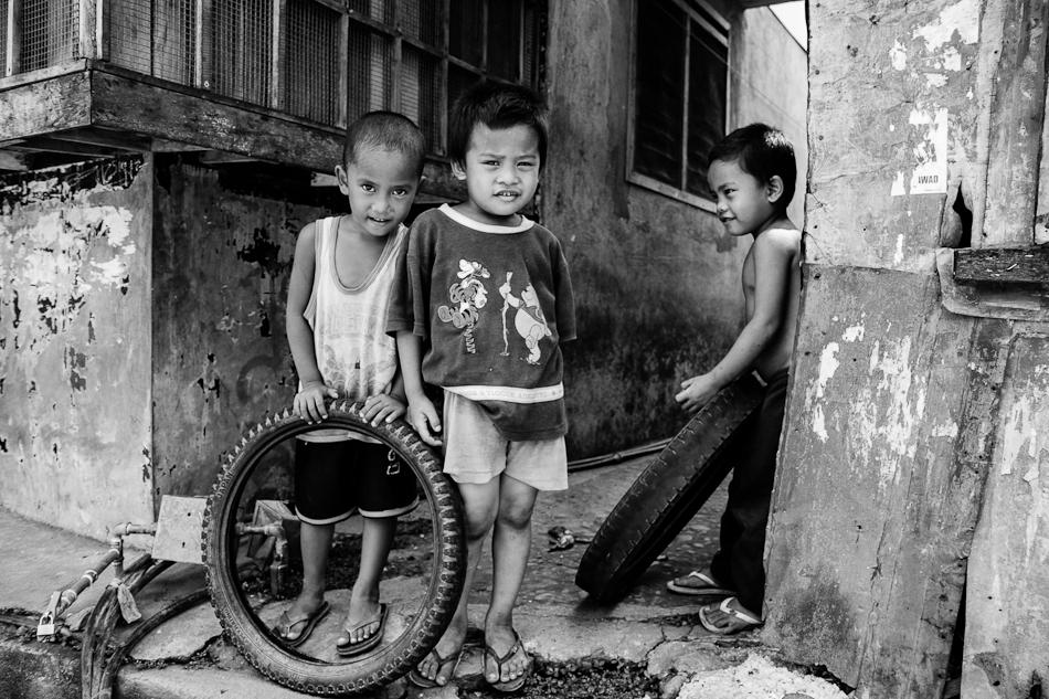 three neighborhood boys on the sidewalk