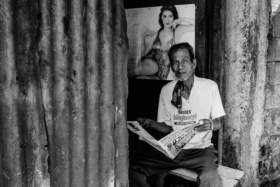 man reading newspaper with a calendar of a beautiful woman at the back
