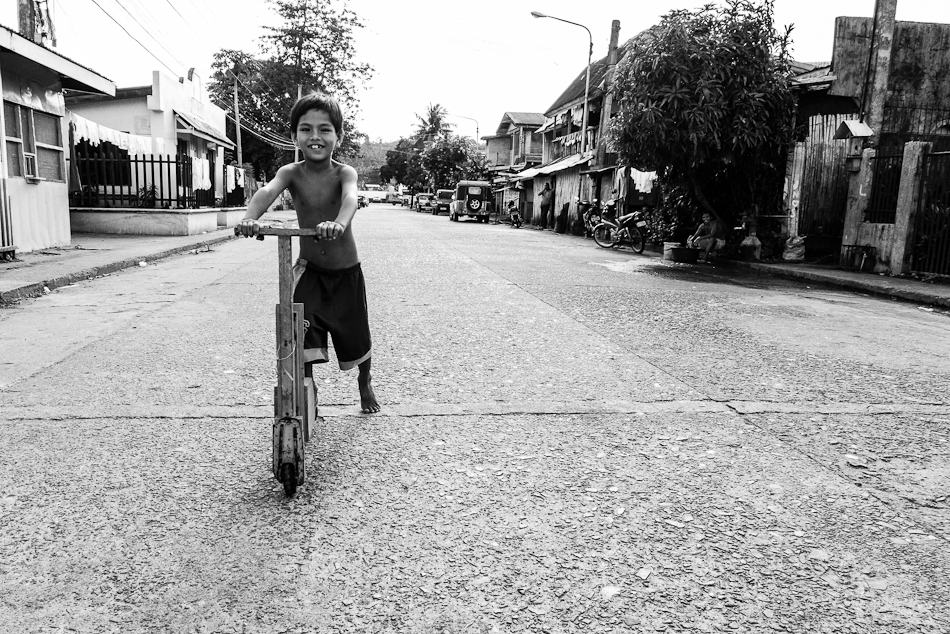 kids with a home made wooden scooter playing in the middle of the road