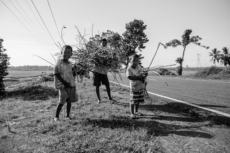 kids gathering firewood by the road side on an early morning