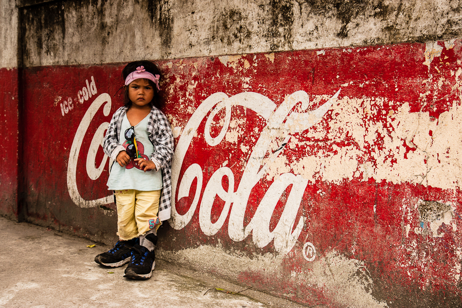 a little girl standing in front of a coca cola advertisement