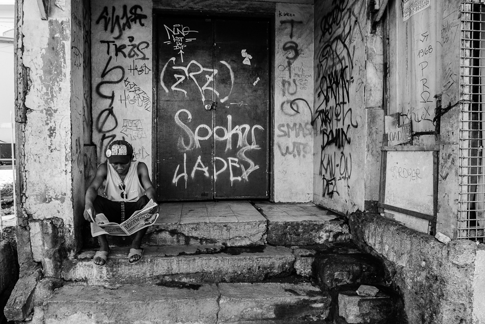 a man reading newspaper on the steps of a graffiti riddled porch