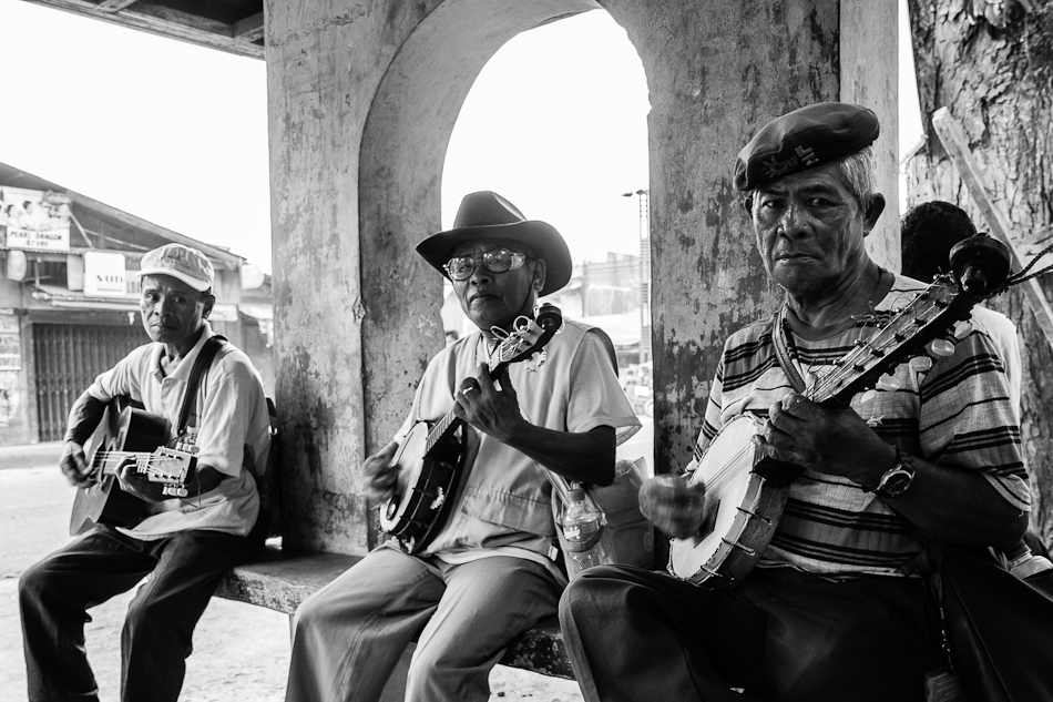 3 musicians playing their music in a bus stop