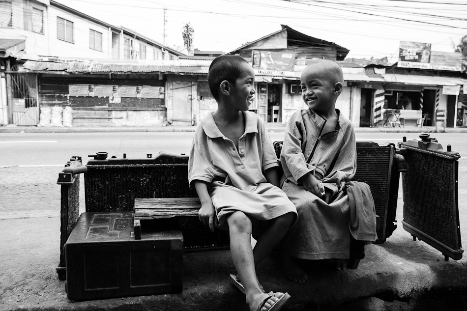 a bald headed boy enjoying a relaxed chat with his brother