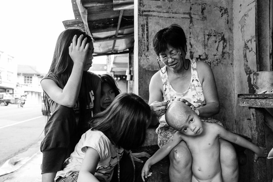 a little boy's head is shaved clean by his grandmother