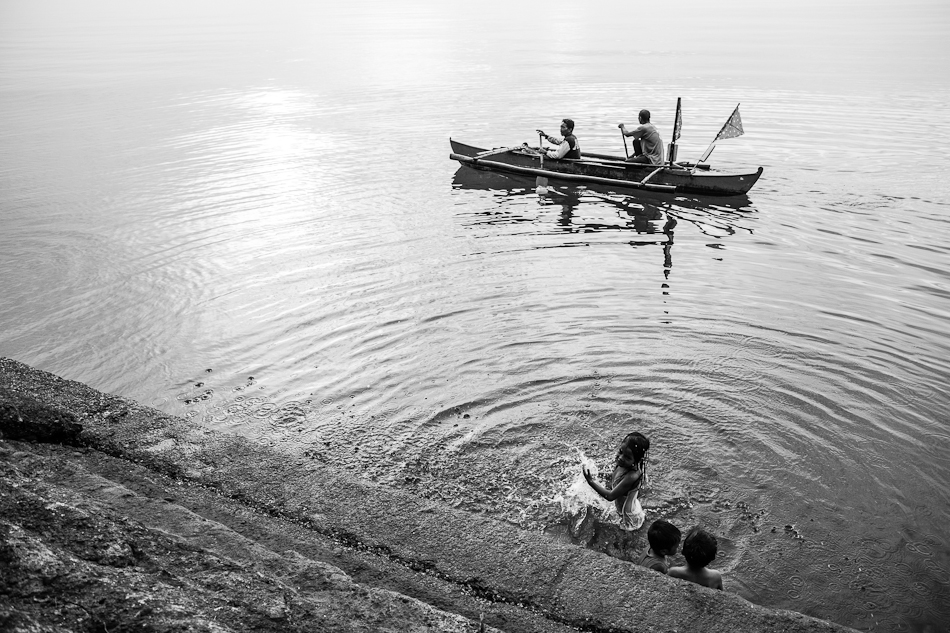 kids taking a bath by the sea wall while a fisherman rows his boat to shore