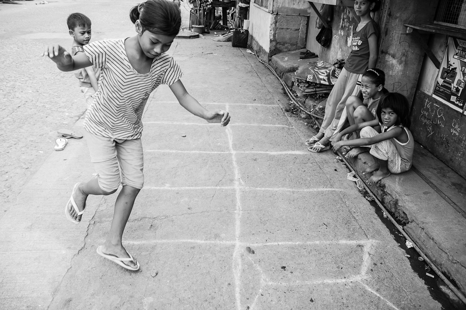 children playing hopscotch along the side of the road