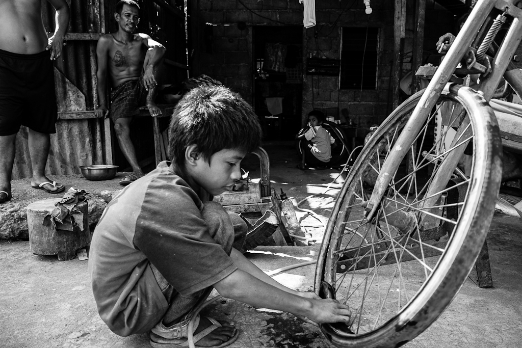 a young boy works at his father's vulcanizing shop