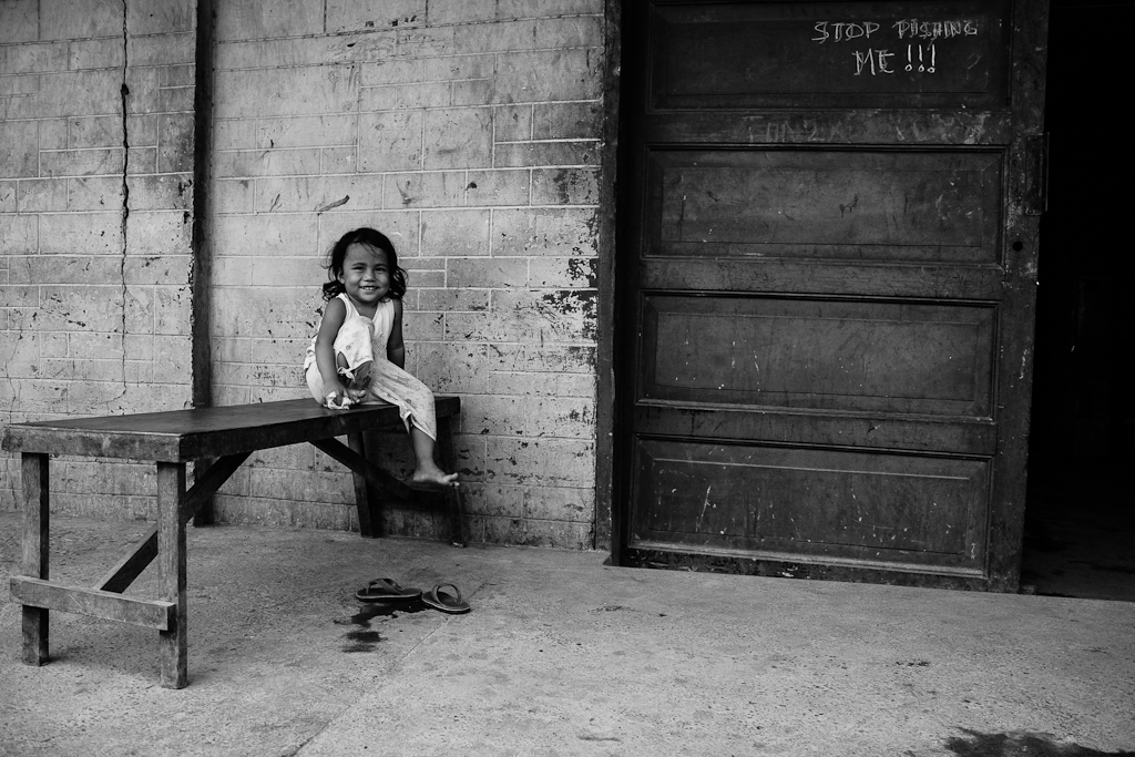 little girl sitting by the door outside her home