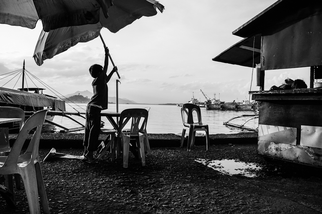 a boy sets up a large umbrella over wooden tables by the pier