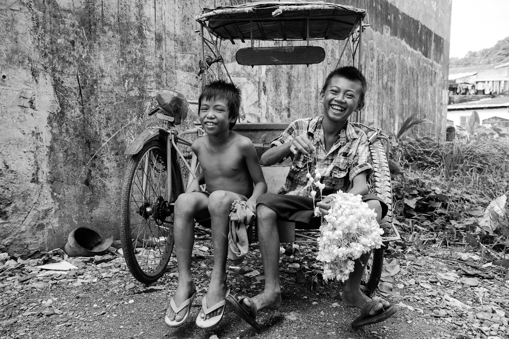 boy selling sampaguita sitting on a tricycle