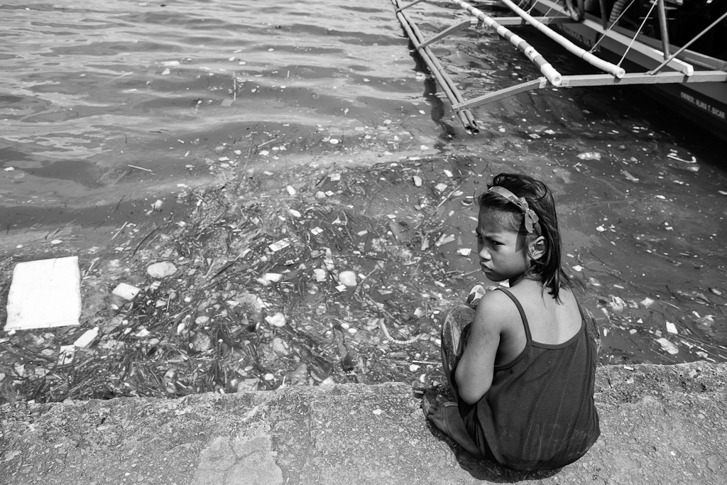 a girl sits on the sea wall looking at all the floating garbage