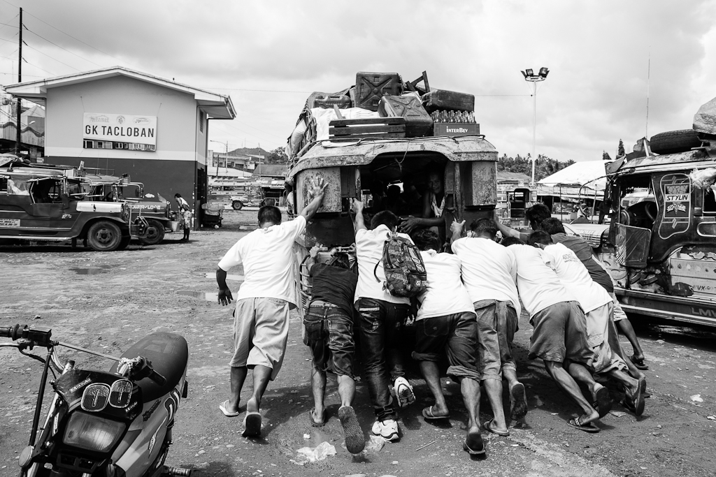 men giving a jeepney a push to get it started