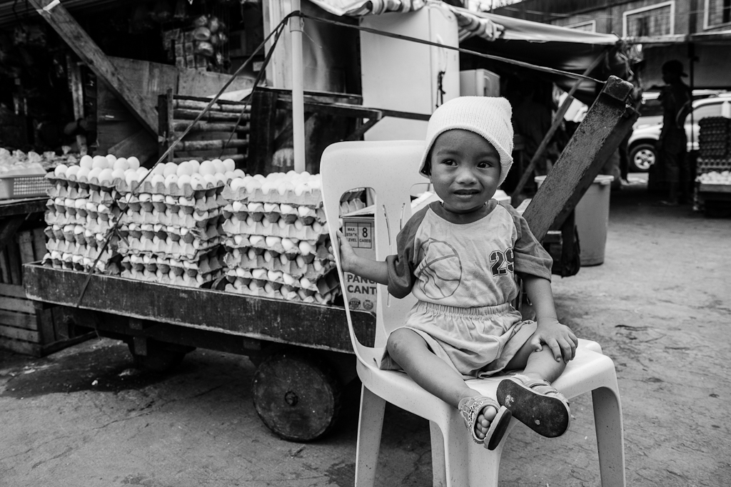 a boy sitting in front of a cart full of eggs