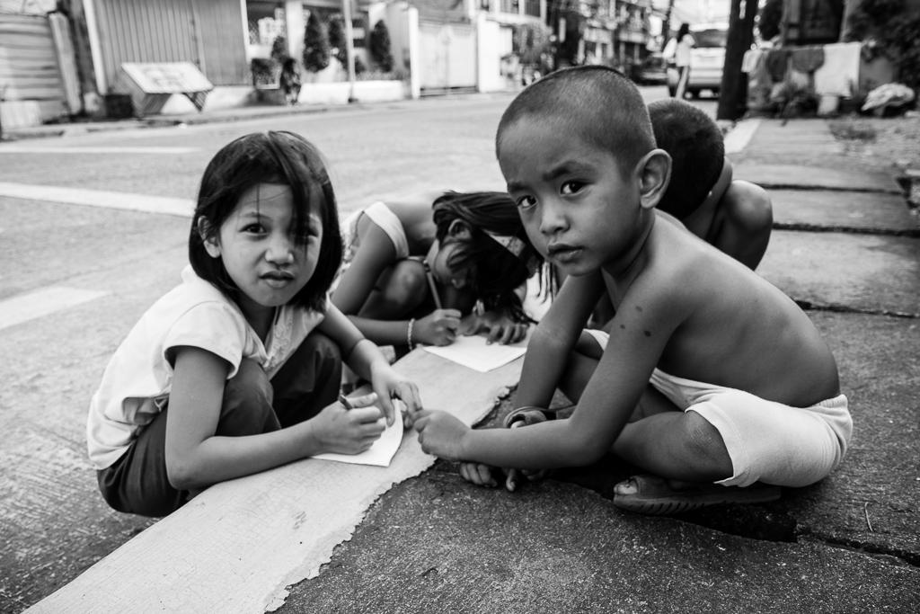 kids passing time making drawings on the sidewalk