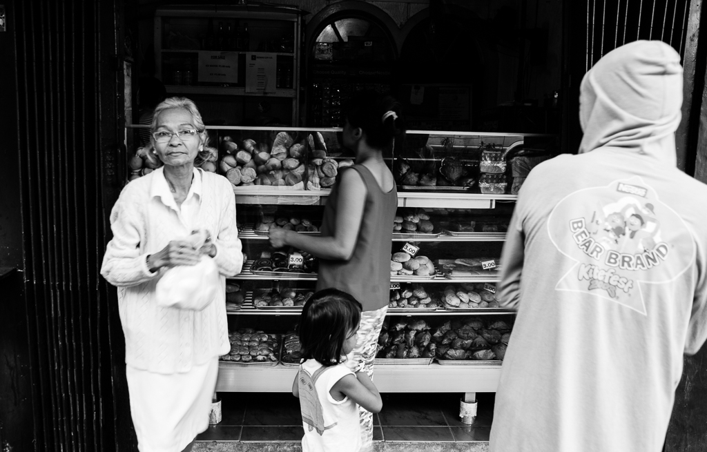 woman buying bread from a local bakeshop