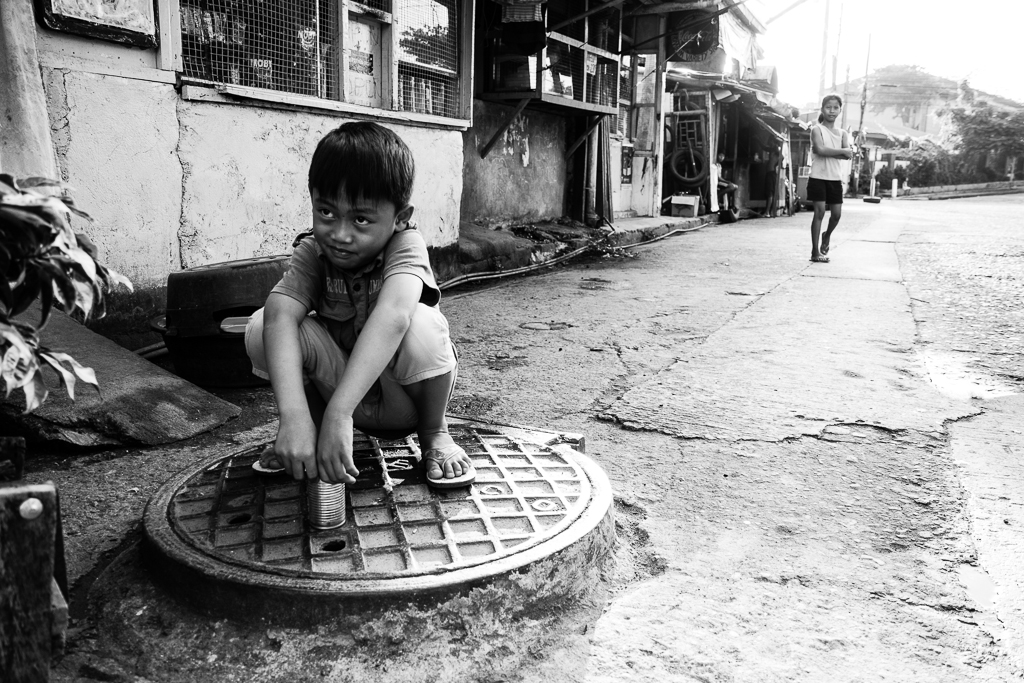 kid sitting on a manhole cover holding an empty tin can