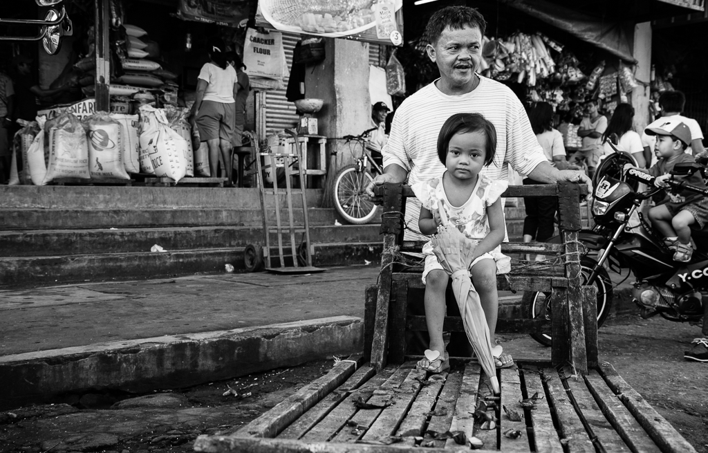 a girl with an umbrella sits on a wooden cart pushed by her father