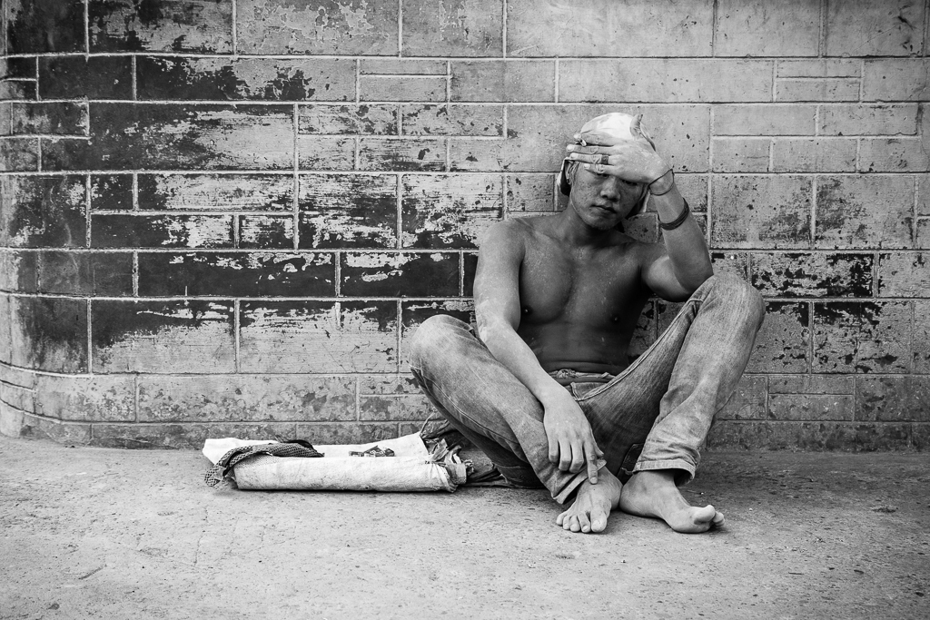 A laborer takes a rest on the sidewalk.  Cement dust covers his body from head to foot